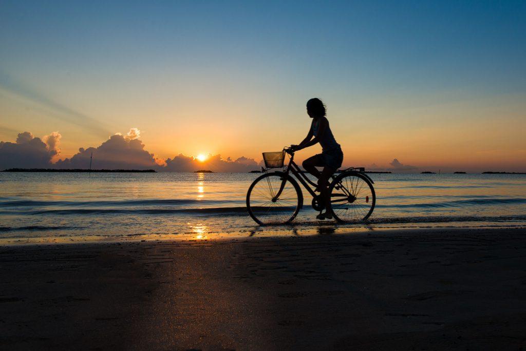 ผู้หญิงปั่นจักรยานริมชายหาด